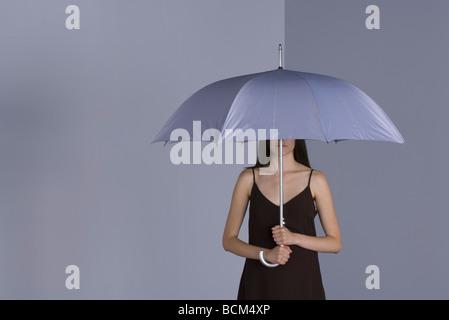Woman under umbrella, le visage partiellement masqué Banque D'Images