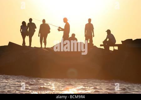 Des gens assis sur le brise-lames au coucher du soleil Banque D'Images