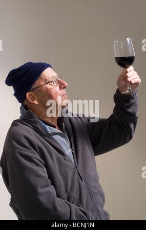 Man dans son 90's à la recherche au verre de vin rouge Banque D'Images