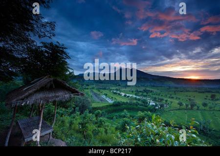 Les rizières en terrasses près de Tirtagangga à l'aube avec le soleil se lever sur le pic volcanique de Lempuyang Banque D'Images
