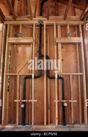 Les tuyaux de plomberie et des drains pour deux lavabos installés dans un mur à l'emplacement de la construction Banque D'Images