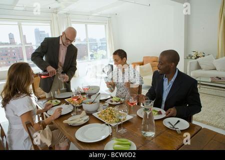 Deux hommes et deux femmes à une table à manger Banque D'Images