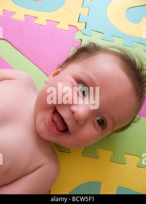 Six mois bébé jouer heureusement jouant sur des tapis colorés Banque D'Images