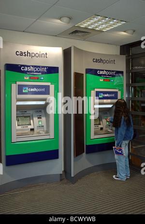 Femme à l'aide de la Lloyds TSB Bank distributeur, Christchurch, Dorset, England, UK