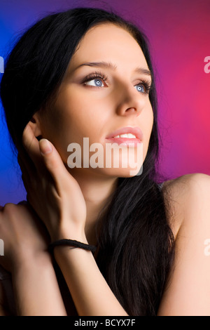 Jeune femme portrait tendre fond bleu et rouge Banque D'Images