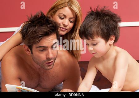 Couple reading boy une histoire au lit Banque D'Images