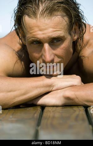 Man resting head on arms sur le côté de la piscine Banque D'Images