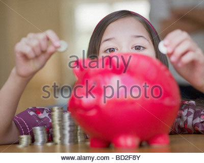 Girl putting coins in piggy bank Banque D'Images