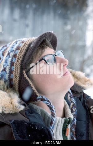 Jeune homme à la recherche dans le ciel enneigé Banque D'Images