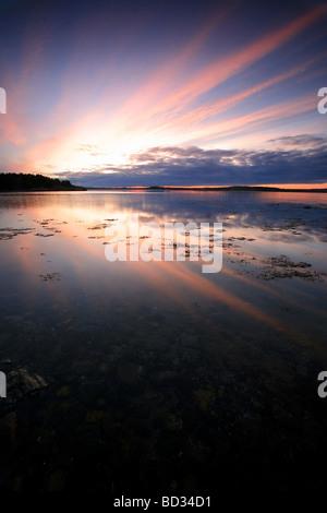 Ciel coloré et réflexions au lever du soleil, à Teibern en Larkollen, Rygge kommune, Østfold fylke, la Norvège. Banque D'Images