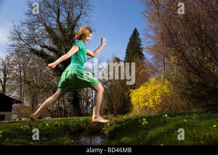 Girl jumping over creek Banque D'Images