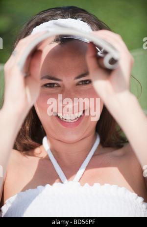 Un blindage extérieur femme ses yeux avec un magazine Banque D'Images