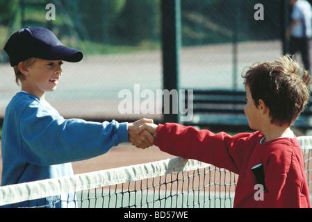 Les filles se serrer la main au filet de tennis Banque D'Images
