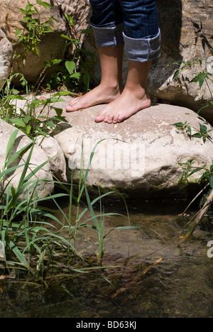 Femme debout, pieds nus sur les rochers de la rivière Banque D'Images