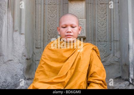Jeune moine bouddhiste se trouve dans un Ronrom porte à East Mebon oriental, l'un des temples d'Angkor à Siem Reap Banque D'Images