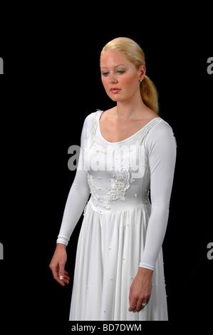 Jeune danseuse de ballet à la recherche vers le bas habillé en robe blanche sur un fond noir isolé Banque D'Images