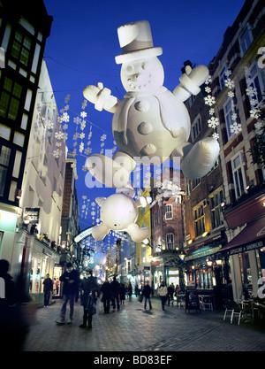Décorations de Noël, y compris les bonshommes gonflables géants, éclairé la nuit à Carnaby Street, dans le West Banque D'Images