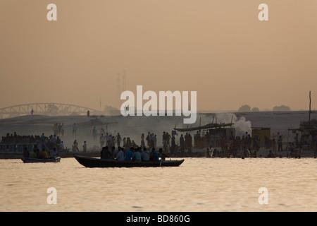Beaucoup de gens assister à des bûchers de crémation qui se profile et le dépôt des restes humains dans le Gange Banque D'Images