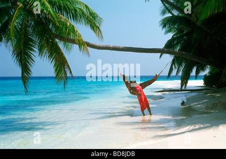 Couple sur l'île de vacances relaxing in hammock on beach in paradise Banque D'Images