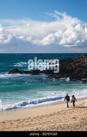 Couple d'âge moyen à pied le long de la plage de Porthmeor tard en soirée le soleil d'été St Ives Cornwall England Banque D'Images