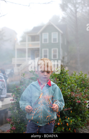 Young boy holding d'artifice Banque D'Images