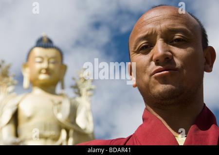 Moine debout devant une statue de Bouddha dans un monastère, le monastère de Likir, Ladakh, le Jammu-et-Cachemire, Banque D'Images