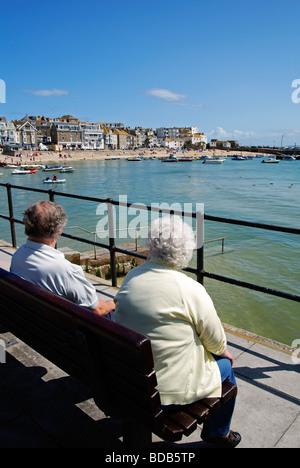 Un vieux couple de retraités assis par le port de St Ives.à Cornwall, uk Banque D'Images