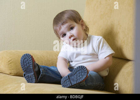 Portrait of young boy sitting on sofa Banque D'Images