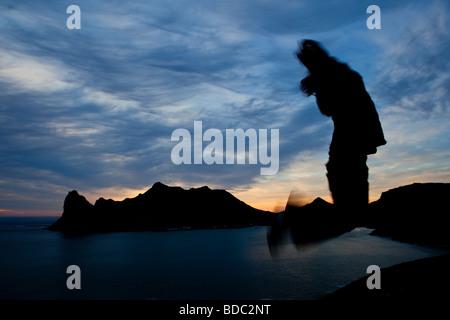 La Silhouette floue d'un garçon sautant avec la Sentinelle en toile de Hout Bay Banque D'Images