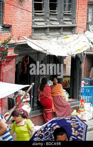 Les gens les femmes en saris colorés colorés debout autour de parler en hamunan dhoka durbar Katmandou Népal Banque D'Images