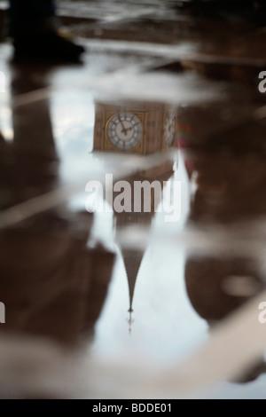 La tour de l'horloge du palais de Westminster (Big Ben) reflète dans une flaque d'eau. Banque D'Images