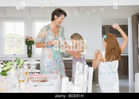 Femme debout avec ses filles jouer à une table à manger Banque D'Images