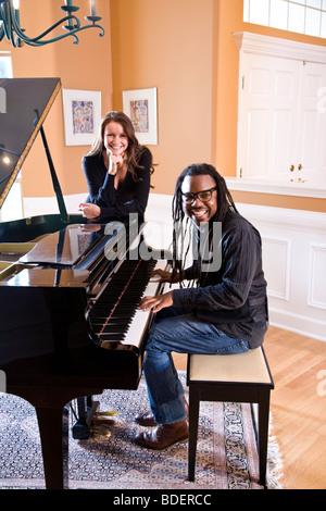 African American man playing piano avec l'amie à l'écoute Banque D'Images