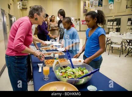 Selena Pina, une mère de quatre sans-abri et ses enfants font la queue pour recevoir un dîner préparé par les bénévoles Banque D'Images