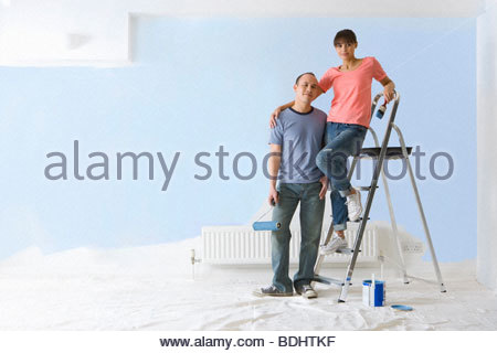 Femme souriante sur l'échelle hugging man à côté de mur peint Banque D'Images