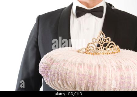 Butler tenant une tiare sur un coussin Banque D'Images