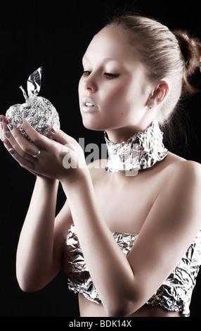 Femme Robot métallique avec Apple. Sur fond sombre. Banque D'Images