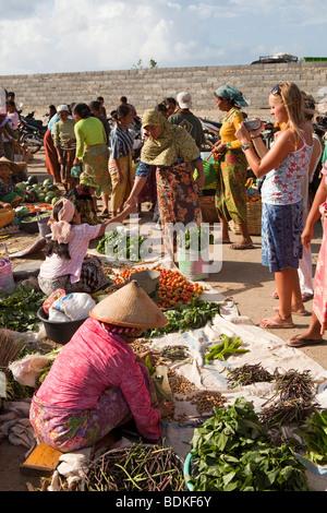 L'Indonésie, Lombok, Kuta, marché hebdomadaire western tourist photographing légumes Banque D'Images