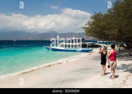 L'Indonésie, Lombok, Gili Trawangan, plage, deux touristes de prendre la photo souvenir Banque D'Images
