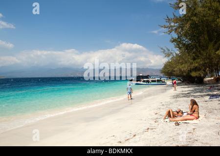 L'Indonésie, Lombok, Gili Trawangan, plage deux baigneurs lying on sand près de inter island ferry boats Banque D'Images