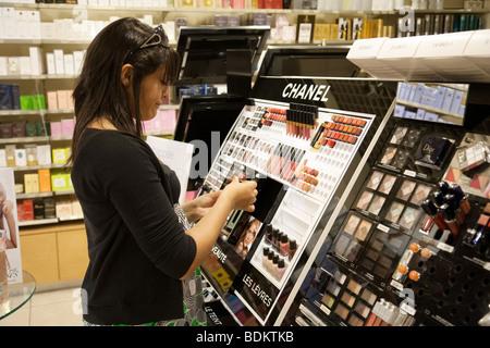 Une adolescente l'achat de cosmétiques dans une pharmacie, Paris, France Banque D'Images