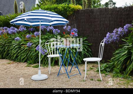 Table et chaises dans le jardin d'un café français sur l'Ile de Bréhat, Bretagne Banque D'Images