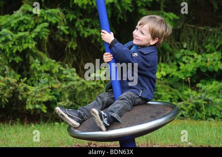 Petit garçon, 2 ans, assis sur un carrousel, Allemagne Banque D'Images