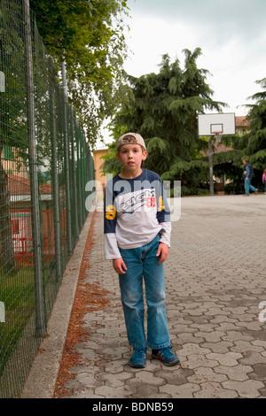 Ricky après l'école un jour de printemps, de basket-ball à l'arrière-plan, c'est le cour de l'école à Armeno, VB, Banque D'Images