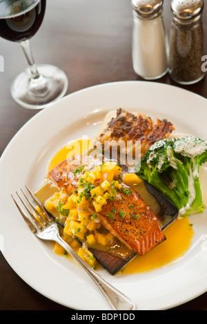 Du saumon cuit sur planche de cèdre avec salsa de mangue, le brocoli, les pommes de terre et un verre de pinot noir Banque D'Images