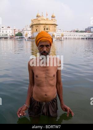 Homme Sikh se baigne dans les eaux - l'Sarovar (réservoir d'eau) -autour du Temple d'Or (Sri Harmandir Sahib) Amritsar. Banque D'Images