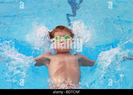 Jeune garçon portant des lunettes vertes en faisant dos à la piscine piscine rencontrez. Banque D'Images