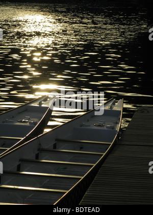 Deux des bateaux de course en bois sur le lac jetée par Sun en Banque D'Images