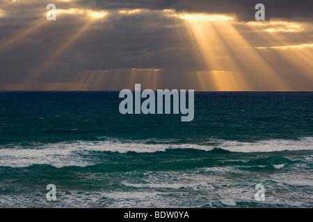 Des faisceaux de lumière traverser une banque de denses nuages noirs au-dessus de l'océan, tête de Mangawhai, Auckland, Banque D'Images