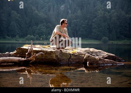 L'homme, mi 40s, accroupie sur un rocher au lac Feldsee dans la Forêt-Noire, Bade-Wurtemberg, Allemagne, Europe